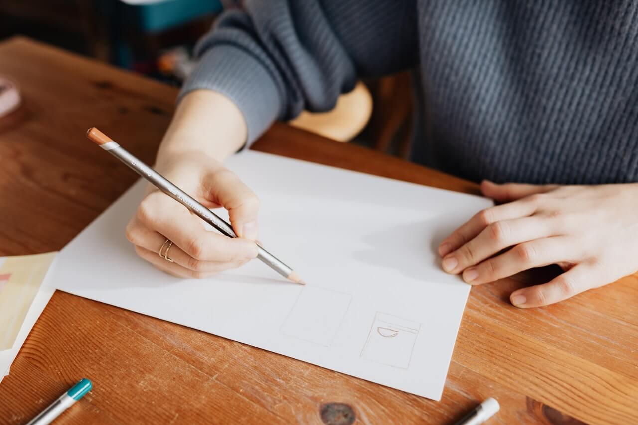 紙にデザインを描いている女性